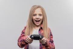 Muchacha con el pelo ondulado rubio largo que siente excitado mientras que juega al videojuego imagenes de archivo