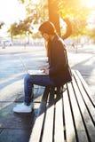 Muchacha con el pelo oscuro largo que se sienta en un parque con un ordenador Imagen de archivo libre de regalías