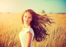 Muchacha con el pelo que sopla que disfruta de la naturaleza