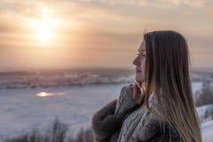 Muchacha con el pelo recto largo contra la perspectiva de un cielo de la tarde del invierno Imagen de archivo libre de regalías