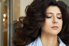 Muchacha con el pelo rizado largo Muchacha magnífica elegante en el salón de belleza de lujo Muchacha con el pelo rizado largo At fotografía de archivo