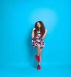 Muchacha con el pelo rizado que presenta en estudio Fotografía de archivo libre de regalías