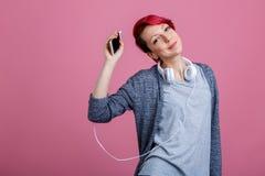 Muchacha con el pelo rojo que escucha la música en los auriculares que aumentan su mano que detiene el teléfono Imagen de archivo
