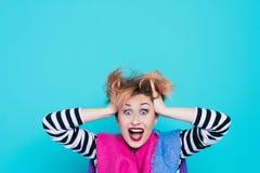 Muchacha con el pelo rojo que lleva a cabo su grito principal Tensión e histérico Emociones negativas Tiro del estudio fotografía de archivo