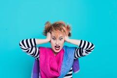Muchacha con el pelo rojo que lleva a cabo su grito principal Tensión e histérico Emociones negativas Tiro del estudio foto de archivo libre de regalías