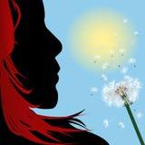 Muchacha con el pelo rojo que sopla sobre el diente de león Foto de archivo libre de regalías