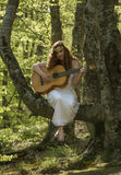 Muchacha con el pelo rojo que toca la guitarra Imagenes de archivo