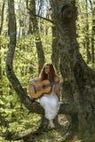 Muchacha con el pelo rojo que toca la guitarra Imagen de archivo