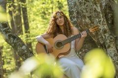 Muchacha con el pelo rojo que toca la guitarra Foto de archivo