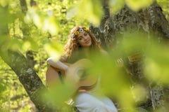Muchacha con el pelo rojo que toca la guitarra Foto de archivo libre de regalías