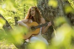 Muchacha con el pelo rojo que toca la guitarra Fotos de archivo