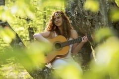 Muchacha con el pelo rojo que toca la guitarra Fotografía de archivo libre de regalías