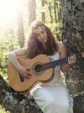 Muchacha con el pelo rojo que toca la guitarra Fotografía de archivo