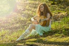 Muchacha con el pelo rojo que toca la guitarra Imagen de archivo libre de regalías