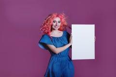 Muchacha con el pelo rosado con la hoja blanca en el fondo de la lila, lugar para el texto Imagen de archivo libre de regalías