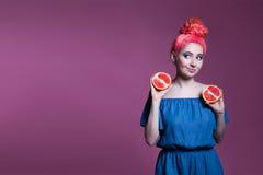 Muchacha con el pelo rosado con mitades del pomelo en el fondo de la lila, lugar para el texto Imágenes de archivo libres de regalías