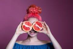 Muchacha con el pelo rosado con mitades del pomelo en el fondo de la lila, lugar para el texto Imagen de archivo libre de regalías