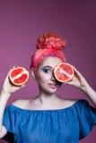 Muchacha con el pelo rosado con mitades del pomelo en el fondo de la lila, lugar para el texto Imagen de archivo