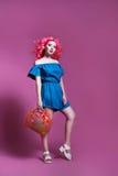Muchacha con el pelo rosado en vestido azul con el bolso en el fondo de la lila, lugar para el texto Imagenes de archivo