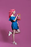 Muchacha con el pelo rosado en vestido azul con el bolso en el fondo de la lila, lugar para el texto Fotos de archivo