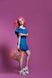 Muchacha con el pelo rosado en vestido azul con el bolso en el fondo de la lila, lugar para el texto Imagen de archivo