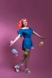 Muchacha con el pelo rosado en vestido con los balones de aire en fondo de la lila, Imagen de archivo libre de regalías