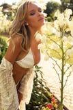 Muchacha con el pelo rubio en el traje de natación, relajándose en jardín del verano fotografía de archivo