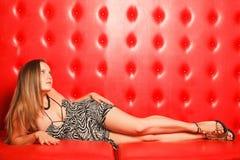 Muchacha con el pelo rubio largo que miente en el sofá Imagen de archivo libre de regalías