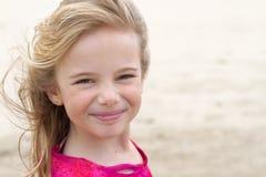 Muchacha con el pelo rubio que sonríe en la playa Imágenes de archivo libres de regalías