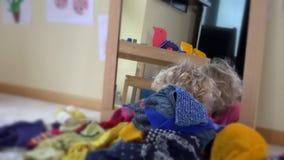 Muchacha con el pelo rubio rizado que miente cerca del espejo y de la ropa colorida que caen abajo almacen de video