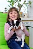 Muchacha con el perrito del dogo Imagen de archivo