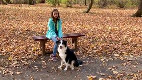 Muchacha con el perrito en parque metrajes