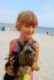 Muchacha con el perro de yorkshire en la playa Fotografía de archivo libre de regalías