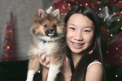 Muchacha con el perro dentro de su casa Foto de archivo