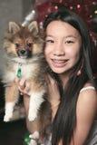 Muchacha con el perro dentro de su casa Imagen de archivo libre de regalías