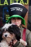 Muchacha con el perro en el día de St Patrick s Imagenes de archivo