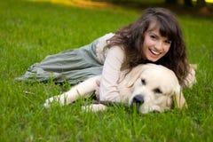 Muchacha con el perro en la hierba Imágenes de archivo libres de regalías