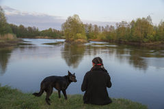 Muchacha con el perro en la orilla fotografía de archivo libre de regalías