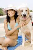 Muchacha con el perro en la playa Imágenes de archivo libres de regalías