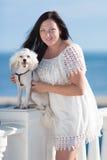 Muchacha con el perro en orilla del mar Fotografía de archivo libre de regalías