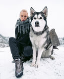 Muchacha con el perro grande del malamute en el fondo de rocas en invierno Foto de archivo libre de regalías