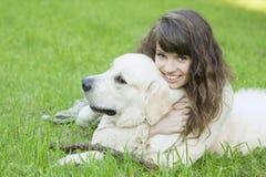 Muchacha con el perro perdiguero de oro en el parque Foto de archivo