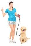 Muchacha con el perro que da un pulgar para arriba Fotos de archivo libres de regalías