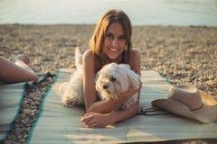 Muchacha con el perro que miente en la playa y la sonrisa imágenes de archivo libres de regalías