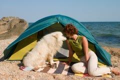 Muchacha con el perro que se sienta cerca de una tienda Foto de archivo libre de regalías