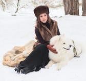 Muchacha con el perro samoed Imagenes de archivo