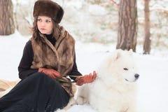 Muchacha con el perro samoed Foto de archivo