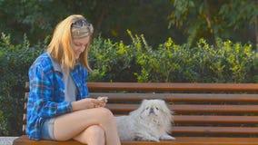 Muchacha con el perro usando un teléfono celular al aire libre