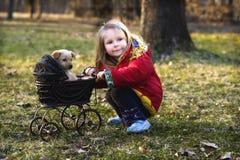 Muchacha con el perro y el cochecito de niño   Imagen de archivo