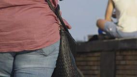 Muchacha con el peso adicional que camina abajo de la calle y que fuma sosteniendo el cigarrillo disponible almacen de metraje de vídeo